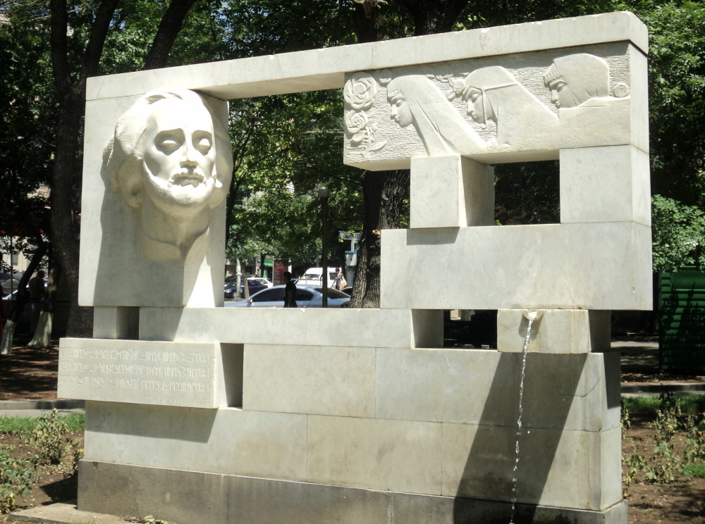 A Soviet-era fountain monument to Sayat Nova in Yerevan, next to a music school named after him, featuring the bard facing three young ladies, each representing one of the South Caucasus nations